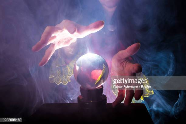 midsection of female fortune teller by crystal ball - paranormal stock pictures, royalty-free photos & images