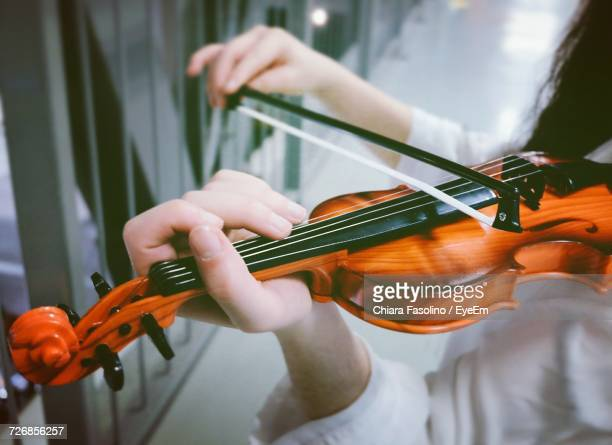 Midsection Of Female Violinist Playing Violin By Fence