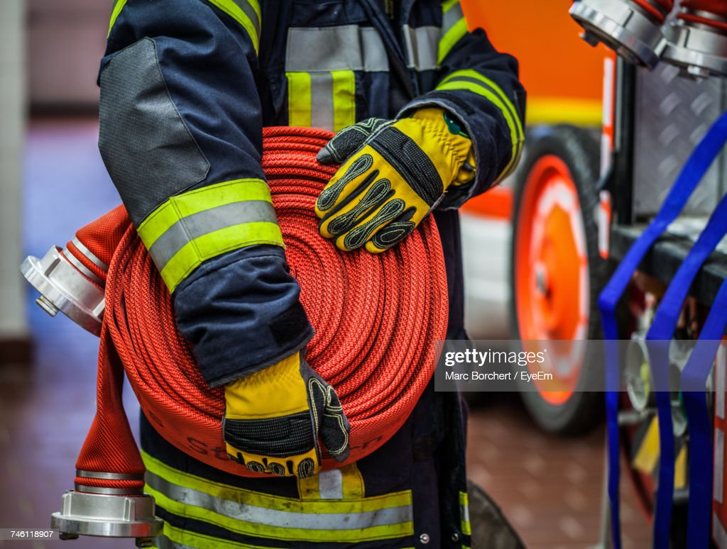 Midsection Of Firefighter Holding Hose At Fire Station : Stock Photo