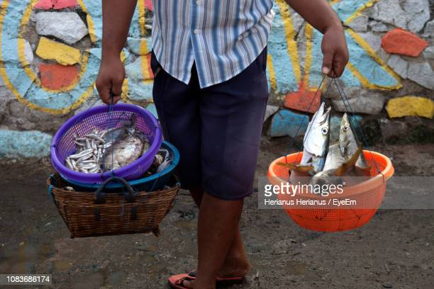Midsection Of Fisherman Carrying Seafood In Containers