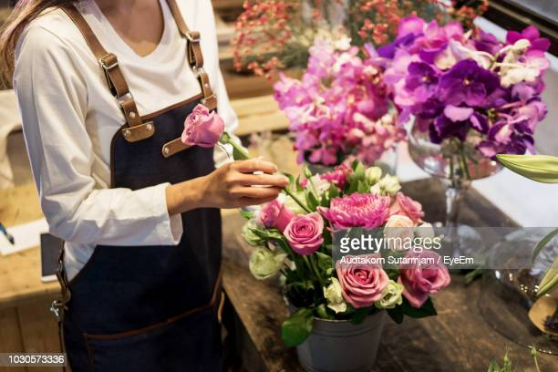 midsection of florist putting rose in bucket on table - putting stock photos and pictures