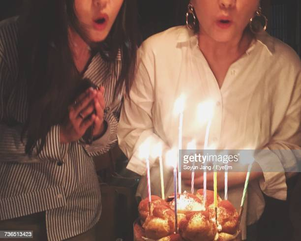 Midsection Of Friends Blowing Candles On Birthday Cake At Home