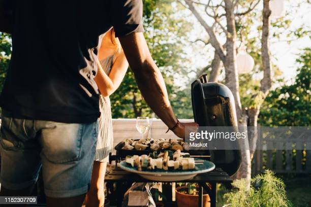 midsection of friends grilling vegetables in barbecue for dinner party - barbecue photos et images de collection