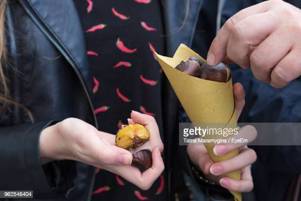 midsection of friends holding chestnuts - castanhas imagens e fotografias de stock