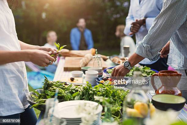 Midsection of friends preparing food at dining table in backyard