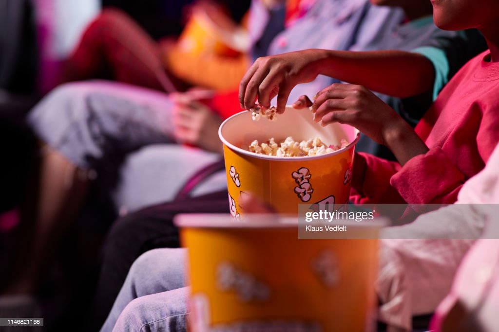 Midsection of friends sharing popcorn while sitting in theater : Stock Photo