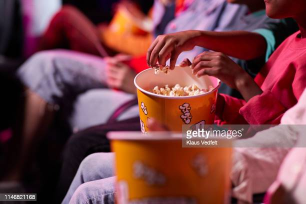 midsection of friends sharing popcorn while sitting in theater - industria cinematografica foto e immagini stock