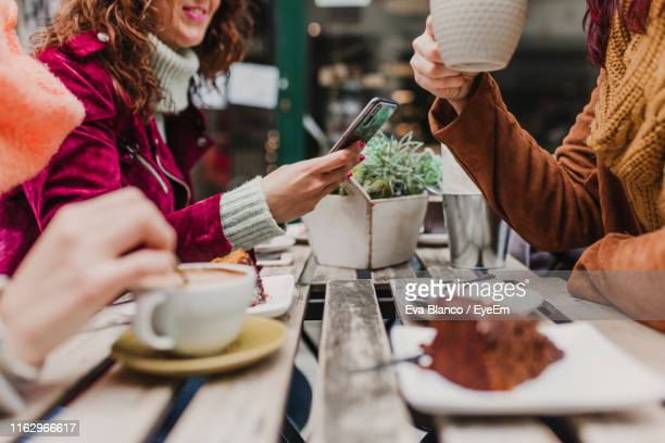 midsection of friends sitting at sidewalk cafe - female friendship stock pictures, royalty-free photos & images