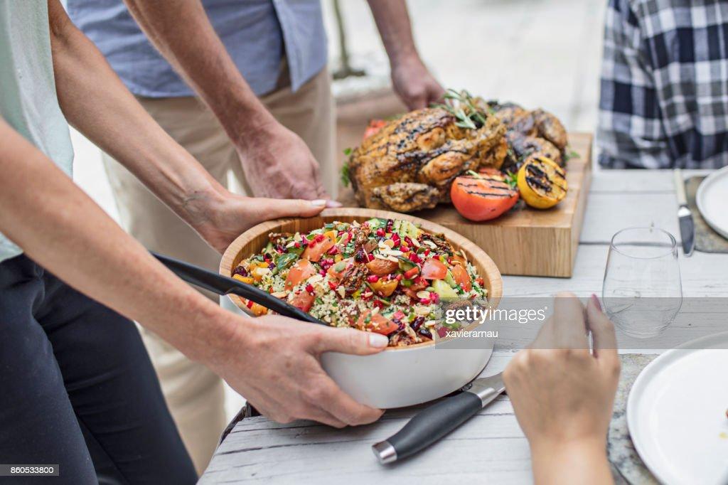 Meio de amigos com comida na mesa de jantar : Foto de stock