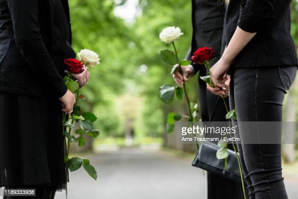 midsection of friends with roses standing on footpath - mort concepts photos et images de collection