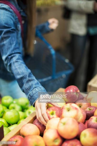 Midsection of girl buying fresh apples in supermarket