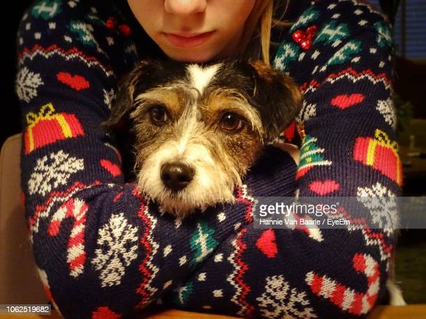 Midsection Of Girl Embracing Dog At Home