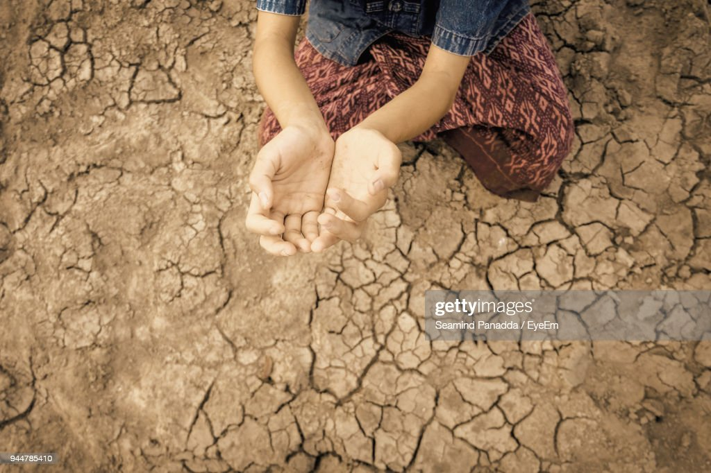Midsection Of Girl Gesturing While Kneeling On Arid Field : Stock Photo
