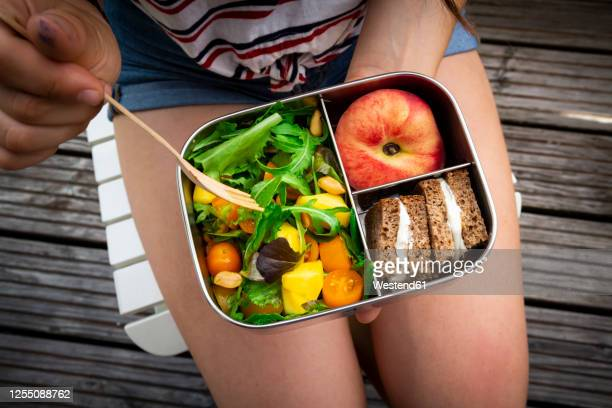 midsection of girl having healthy lunch while sitting on bench - lunch box stock pictures, royalty-free photos & images