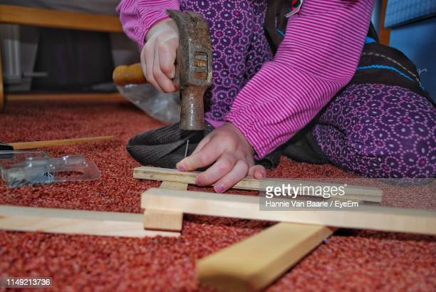 Midsection Of Girl Hitting Nail In Wooden Plank With Hammer At Home