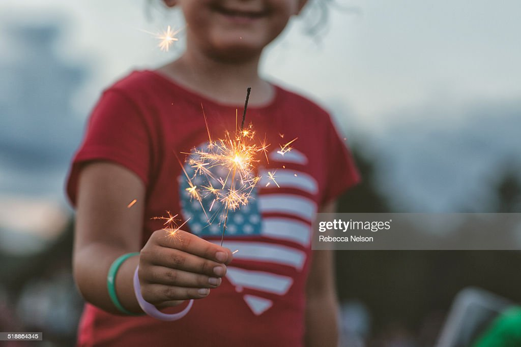midsection of girl holding lit sparkler : Stock Photo