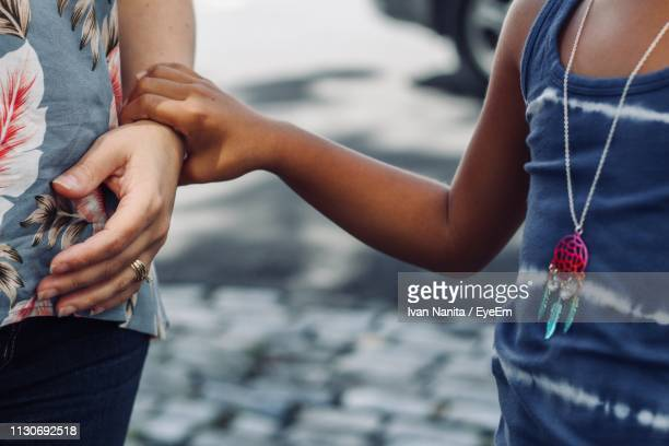 midsection of girl holding mother hand - ペンダント ストックフォトと画像
