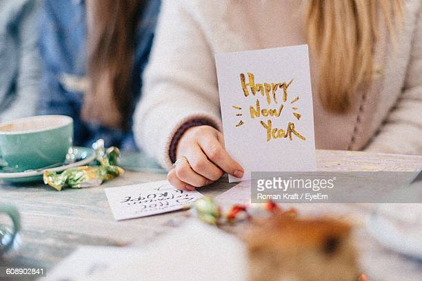 midsection of girl holding new year card at table - holiday card stock photos and pictures