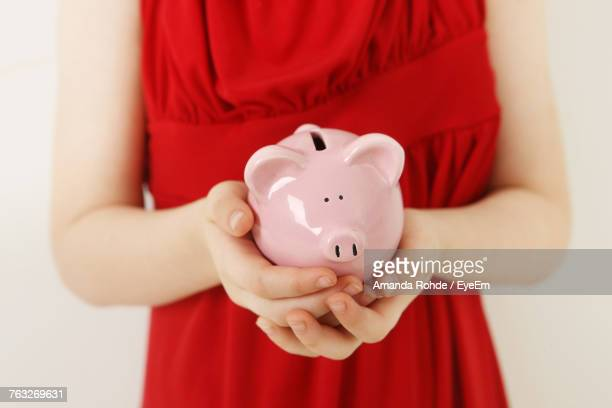 Midsection Of Girl Holding Piggy Bank