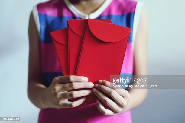 midsection of girl holding red envelopes - midsection stock pictures, royalty-free photos & images