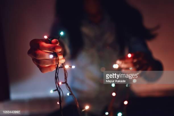 midsection of girl holding string lights in her hand - kerstverlichting stockfoto's en -beelden