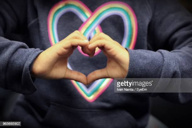 Midsection Of Girl Making Heart Shape With Hands
