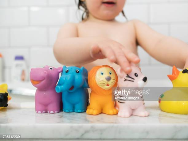 Midsection of girl playing with rubber toys in bathtub
