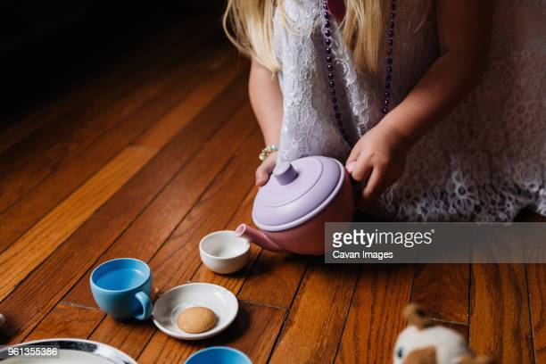 Midsection of girl playing with toys at home