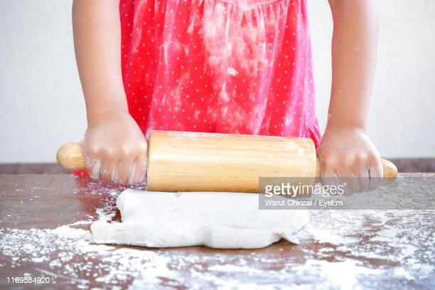 midsection of girl preparing dough with rolling pin on table - rolling stock pictures, royalty-free photos & images