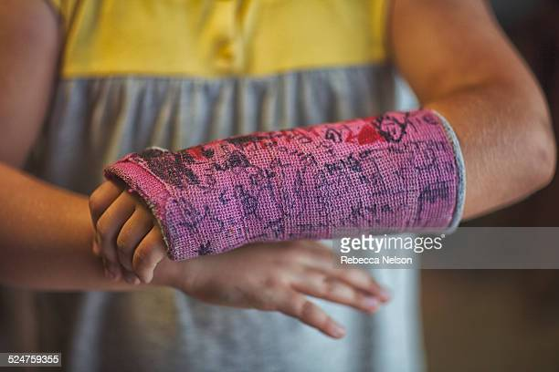 midsection of girl showing her signed arm cast