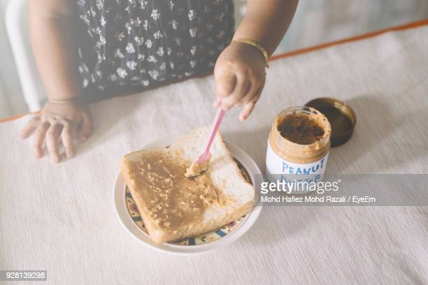 midsection of girl spreading peanut butter on bread in plate at home - nuts models stock photos and pictures