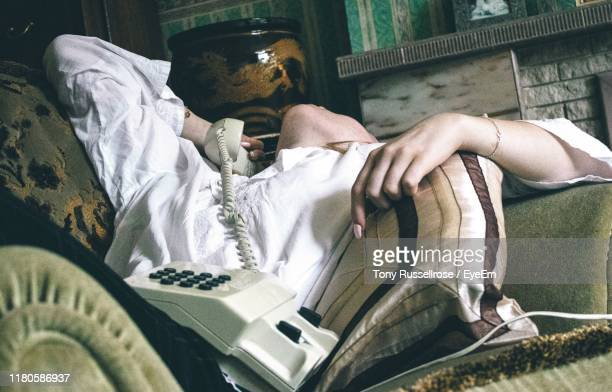 midsection of girl talking on landline phone while lying on sofa - landline phone stock pictures, royalty-free photos & images