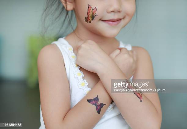 midsection of girl with artificial butterfly tattoos on body parts at home - fake stock pictures, royalty-free photos & images