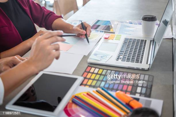 midsection of graphic designers working on table - graphic designer stock pictures, royalty-free photos & images