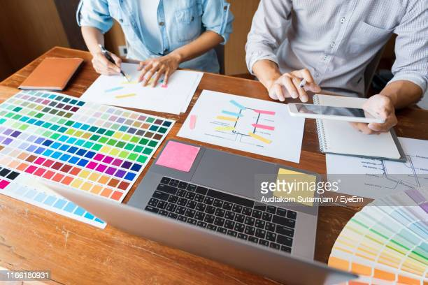 midsection of graphical designers working on table - ウェブデザイナー ストックフォトと画像