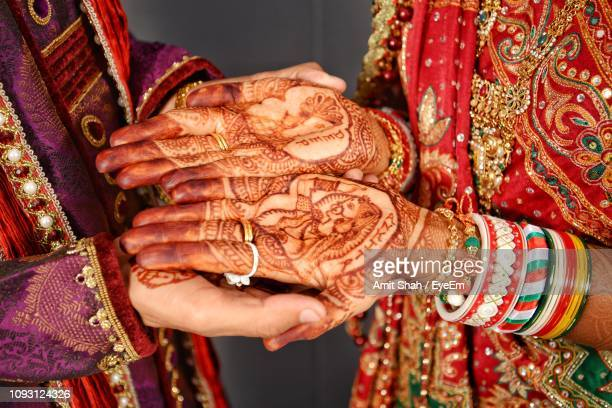 midsection of groom holding bride hands with henna tattoo - wedding vows stock pictures, royalty-free photos & images