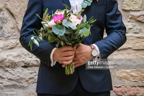 midsection of groom holding flower bouquet - low section stock pictures, royalty-free photos & images