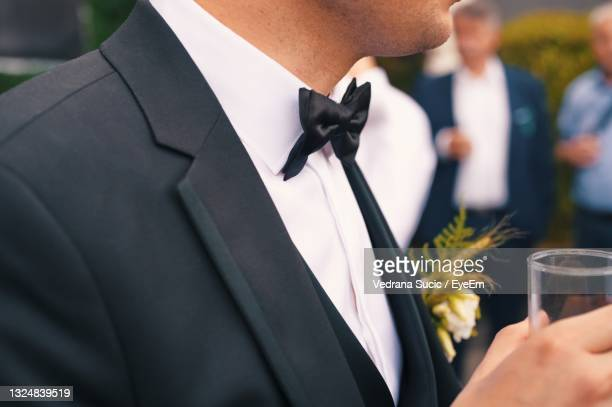 midsection of groom in formal suit holding glass of drink - formal stock pictures, royalty-free photos & images