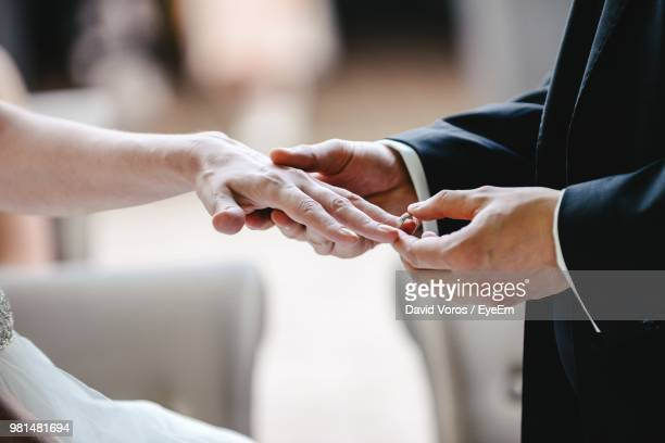 midsection of groom putting ring in bride finger - putting stock photos and pictures