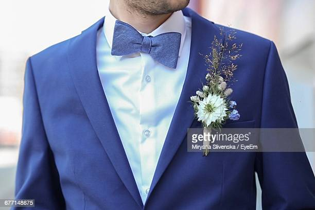 Midsection Of Groom Wearing Suit With Boutonniere