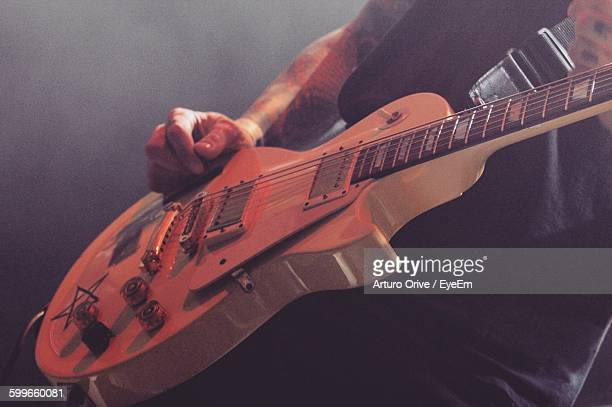 midsection of guitarist performing at music concert - modern rock stock pictures, royalty-free photos & images