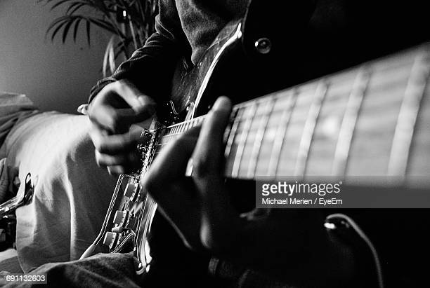 Midsection Of Guitarist Playing Electric Guitar At Home