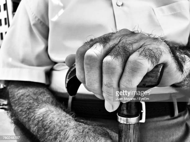 midsection of hairy man holding walking cane - hairy old man stock pictures, royalty-free photos & images
