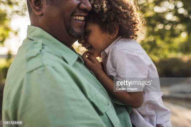 midsection of happy father embracing son while standing at park - mid section stock photos and pictures