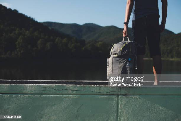 Midsection Of Hiker With Backpack Standing On Retaining Wall By Lake