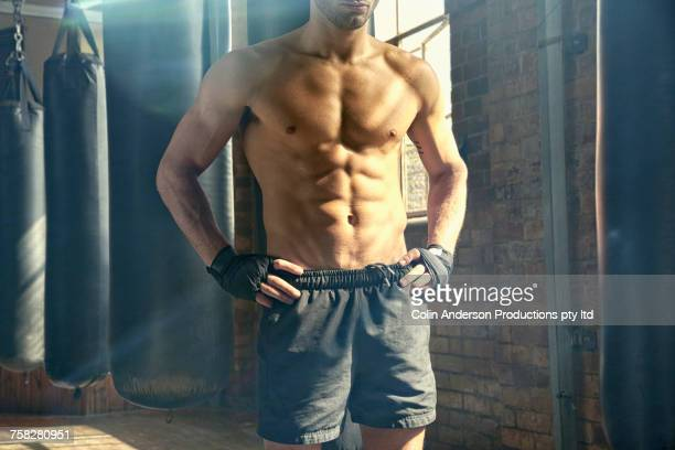 midsection of hispanic man standing near punching bags in gymnasium - sin camisa fotografías e imágenes de stock