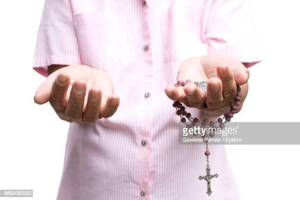 midsection of holding praying against white background - rosary beads stock pictures, royalty-free photos & images
