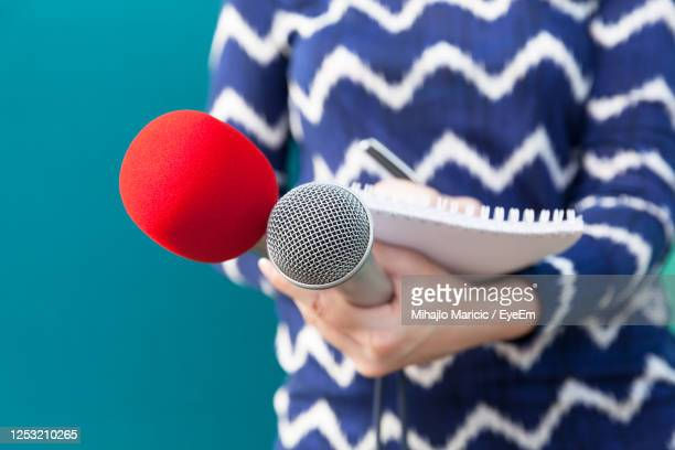midsection of journalist holding microphone and book - journalist photos et images de collection