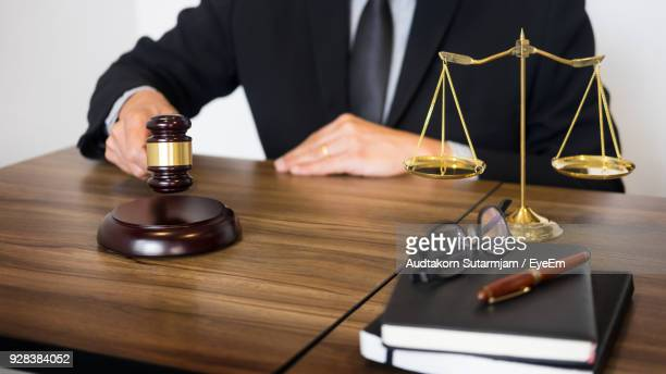 midsection of judge sitting by table at courtroom - mid section stock photos and pictures
