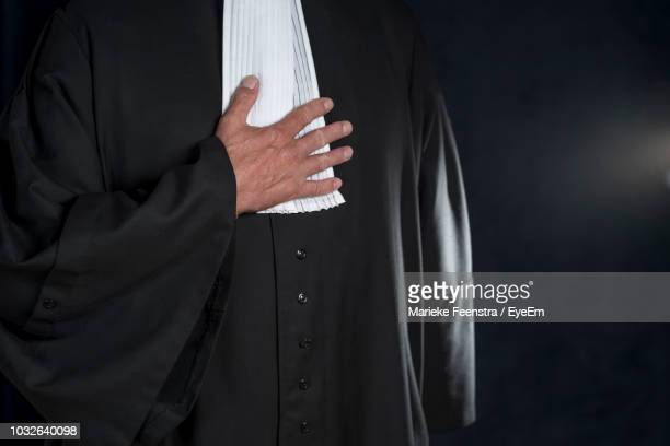 midsection of judge standing against black background - lawyer stock pictures, royalty-free photos & images